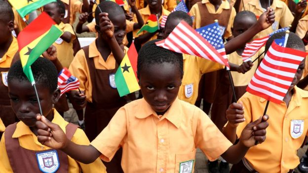 Children carry flags as they greet U.S. first lady Melania Trump on arrival in Accra