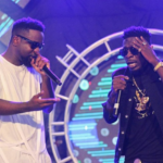 Sarkodie (white) and Shatta Wale perform together at a show