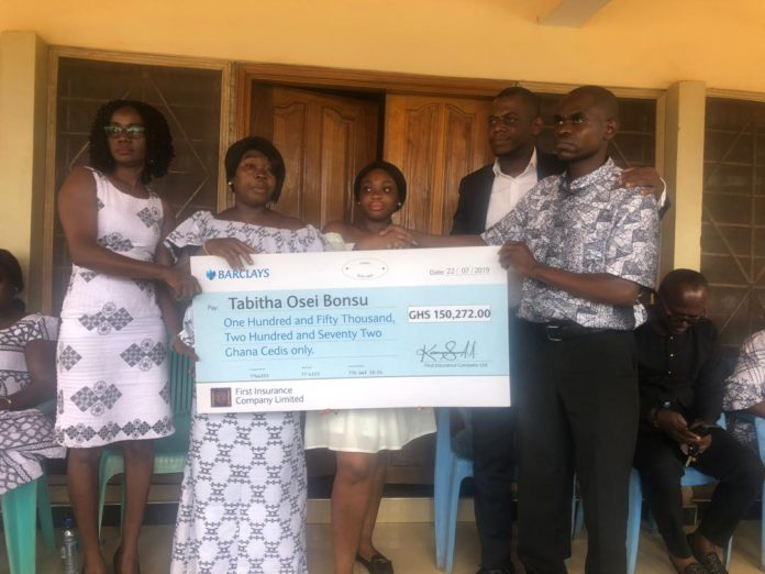 Acting Deputy Head of Business Development at First Insurance, Dela Hosu, presenting the cheque to the family