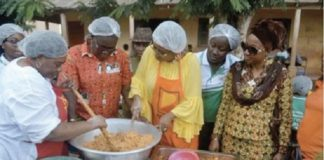 Cynthia Morrison being assisted by Dr Mrs Gertrude Quashigah to prepare the 'gari fotor