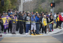 People gather on Las Virgenes Road in Calabasas near the scene of Sunday's helicopter crash.(Mel Melcon / Los Angeles Times)