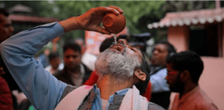 A group of Indians holding a cow urine drinking party