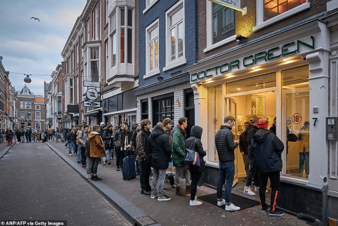 A queue of people line up outside a shop called Doctor Green - one of Holland's famous 'coffee shops' - in the Hague yesterday after the Dutch government announced that many businesses were closing over coronavirus fears