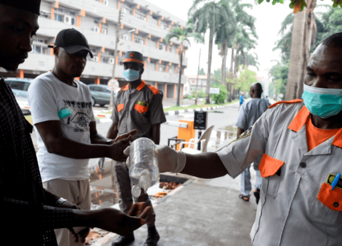 A security guard administering sanitizer to a hospital visitor in Lagos, Nigeria, on Friday.Credit...Pius Utomi Ekpei/Agence France-Presse — Getty Images