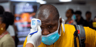 Man being checked with a gun thermometer at a checkpoint because of Coronavirus