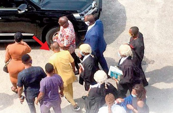 Daniel Obinim (arrowed) approaching his vehicle after yesterday's proceedings
