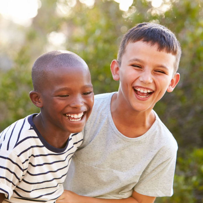 A black boy laughing with a white boy