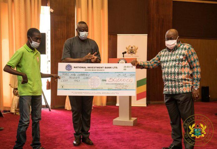 Nana Addo Dankwa Akufo-Addo presenting a cheque to a beneficiary