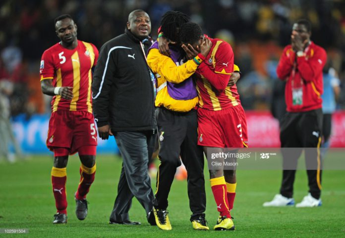 JOHANNESBURG, SOUTH AFRICA – JULY 02: Asamoah Gyan is consoled by Derek Boateng after Ghana are knocked out in a penalty shoot-out during the 2010 FIFA World Cup South Africa Quarter Final match between Uruguay and Ghana at the Soccer City stadium on July 2, 2010, in Johannesburg, South Africa. (Photo by Clive Mason/Getty Images)