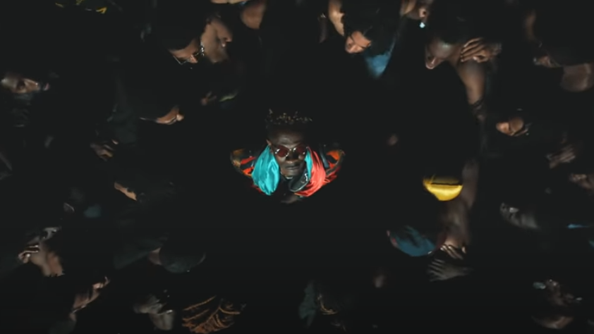Shatta Wale with a Ghana flag around his neck facing up to the camera in the music video for Already with Beyonce