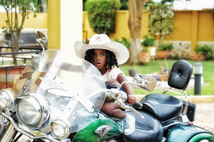 Gifty Anti's daughter, Nyame Anuonyam poses on father's motorbike
