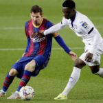 Getafe's Ghanaian midfielder Sabit Abdulai (right) tries to tackle Barcelona's Lionel Messi