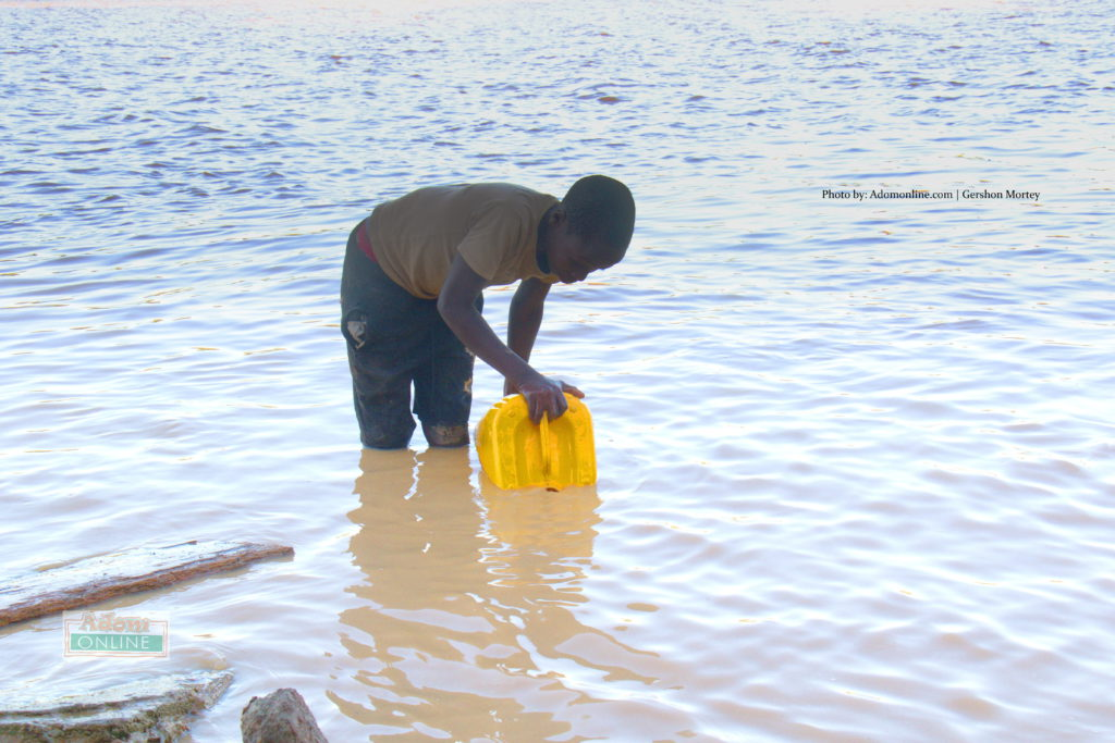Young lad fetches contaminated water from River Pra